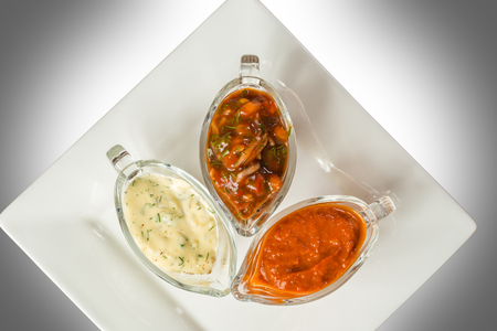 tomato catsup: Various sauces in glass bowls on a white plate
