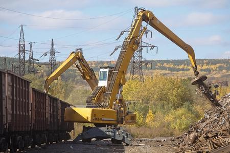 Two yellow excavators working on the scrapyard
