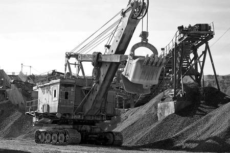 gaining: Excavator bucket gaining rubble. Black and white photo