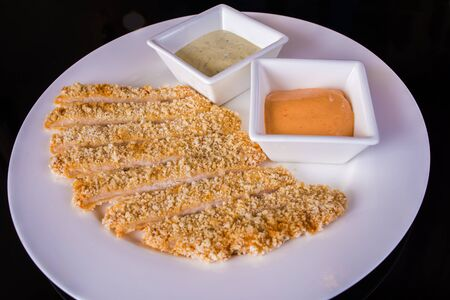 sauces: Breaded fish fillets with sauces on the table
