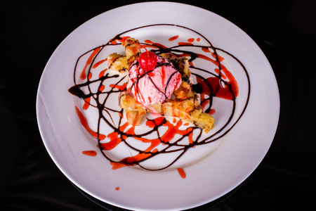 Cake with Scoop of ice cream with syrup and cherry on top