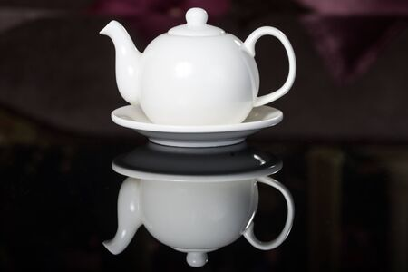 homeware: Close-up of White Teapot on a black reflective background