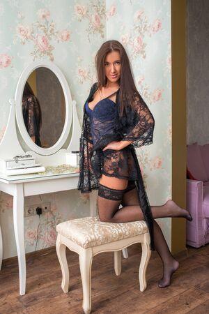 Seductive brunette girl in underwear near vintage boudoir in the room