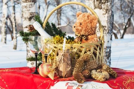Geschenk des neuen Jahres in einem Korb mit Dekorationen auf dem Tisch in einem Wald