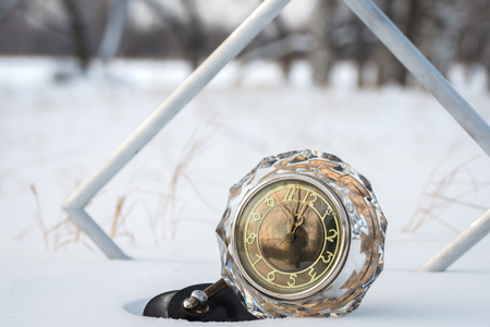 twelve month old: New Years   retro clock with frame in the snow,close up