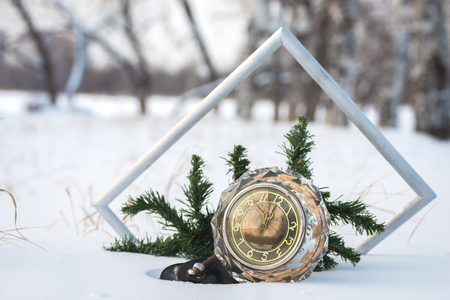 twelve month old: New Years   retro clock with frame and Christmas tree  branch  in the snow,close up Stock Photo