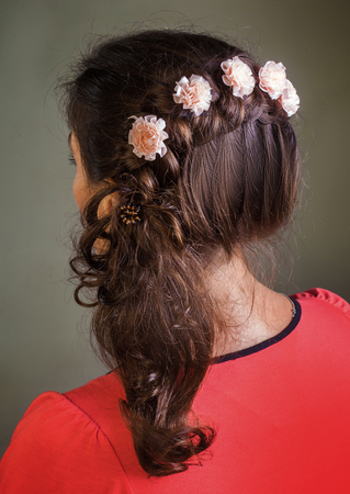 barrettes: Brunette girl with curly hair styling with floral barrettes Stock Photo