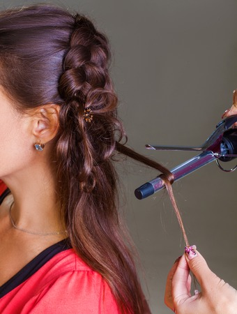 curler: Woman curling hair with electric hair curler Stock Photo