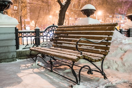 winter park: Bench in winter city park in the evening