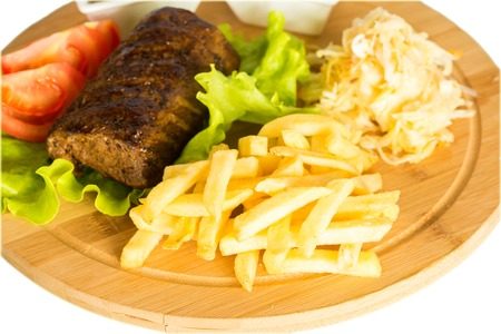 crusted: Close-up of tasty baked meat, tomatoes and french fries on a wooden board