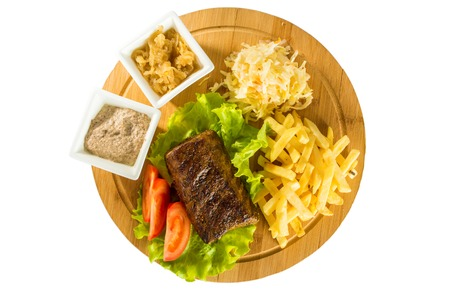 mutton chops: Tasty baked meat, tomatoes, french fries and sauces on a wooden board