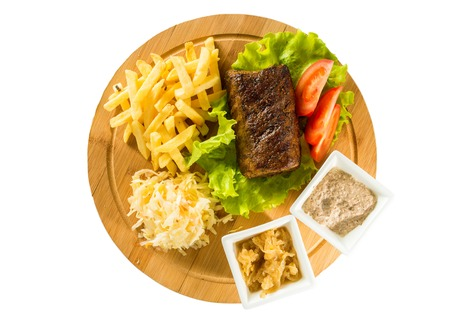 crusted: Tasty baked meat, tomatoes, french fries and sauces on a wooden board
