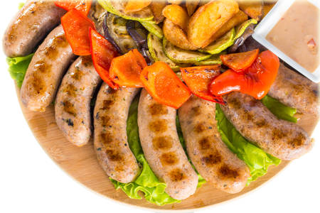 Tasty grilled sausages with vegetables and sauce close up on wooden board