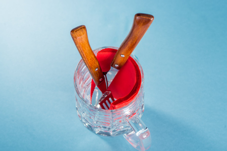 homeware: Cutlery and red napkins in glass beer glass against blue background