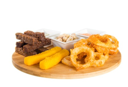 onion rings: Close-up of cheese sticks, onion rings, crackers, salted peanuts and sauce on wooden board