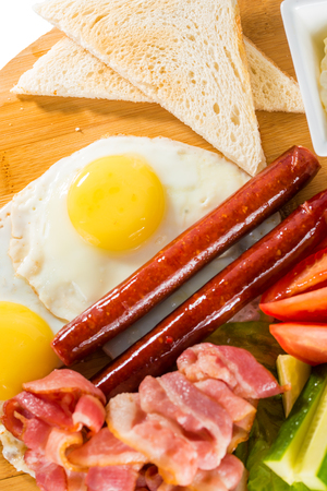 huevos estrellados: Tasty breakfast - toasts, fried eggs, sausages, meat and vegetables on wooden board