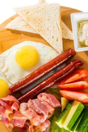 huevos estrellados: desayuno sabroso - tostadas, huevos fritos, salchichas, carne y verduras en la tabla de madera
