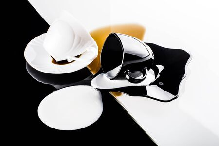 overturn: black and white coffee cups with plates on white and black background Stock Photo