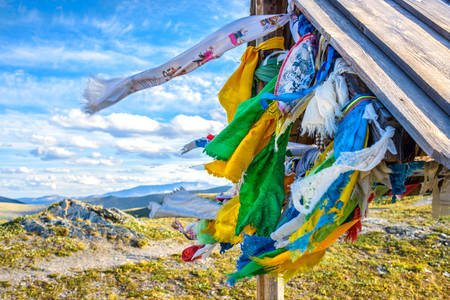 gazebo: Wooden gazebo with colorful flags on the top of mountain Stock Photo