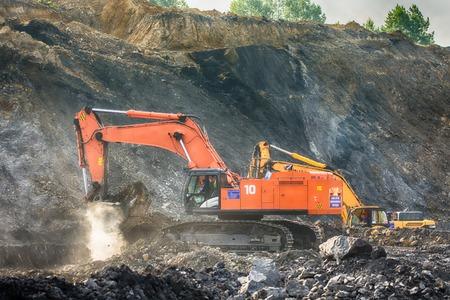 earthmover: Big orange excavator at worksite