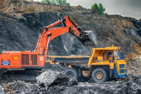 earthmover: NOVOKUZNETSK, RUSSIA - JULY 26, 2016: Big yellow mining trucks and excavators at worksite