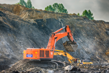 worksite: NOVOKUZNETSK, RUSSIA - JULY 26, 2016 Big orange and yellow excavators at worksite