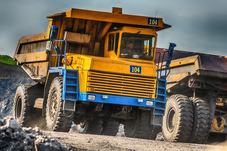 worksite: NOVOKUZNETSK, RUSSIA - JULY 26, 2016: Big yellow mining trucks at worksite