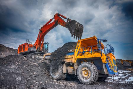 worksite: NOVOKUZNETSK, RUSSIA - JULY 26, 2016: Big yellow mining trucks and excavators at worksite