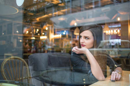 girl looking out window in cafe Stock Photo