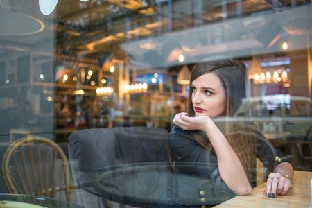 girl looking out window in cafe Standard-Bild