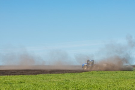 blue tractor plowing field