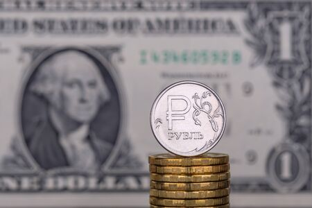 Eine Rubel-Münze vor dem Hintergrund von 1 (einer) Dollar-Banknote.