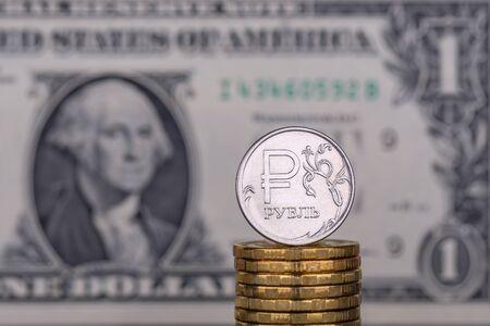 Jedna moneta rubla na tle banknotu 1 (jeden) dolara.
