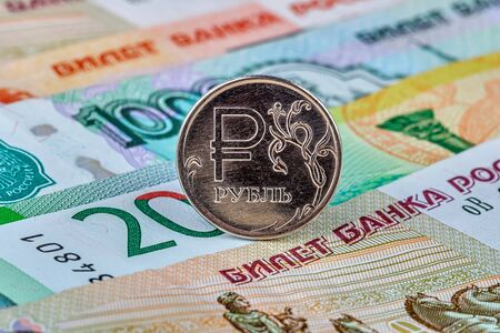 Coin of one russian rouble at paper currency various banknotes background. Фото со стока