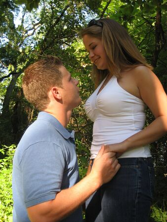Man kneeling in front of woman holding her hand. They are happily looking into eachother's eyes. photo