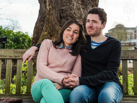 Portrait of Beautiful Young Couple Sitting on a Bench in a Park photo