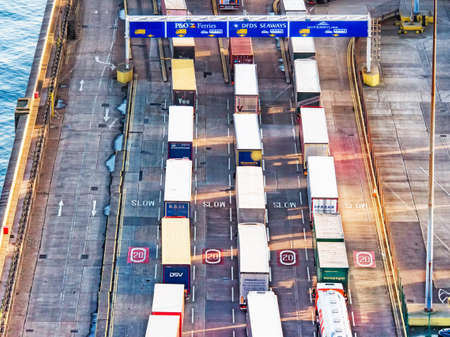 shipped: Line of trucks in sea port with many containers waiting to be shipped Stock Photo