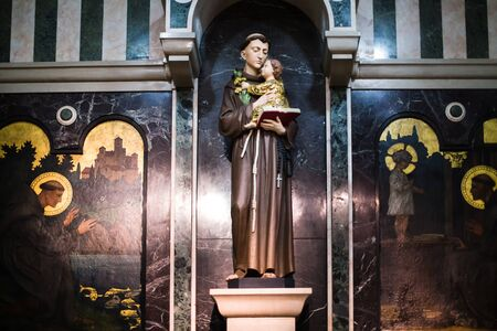 Saint Statue Holding a Baby and Book in Church