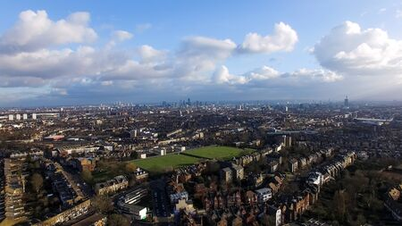 Aerial Urban Downtown View of London City with Green Pitch and Blue Sky Clouds. Landmarks in the Background at Distance Banque d'images
