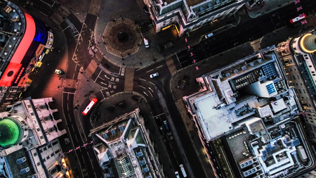 Aerial View Photo of Birds Eye View Flying Over Piccadilly Circus and City Streets at Night in London, England UK