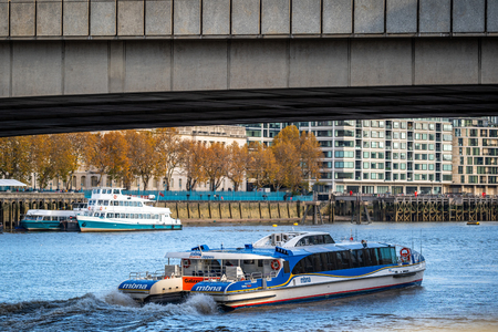 LONDON - NOVEMBER 13 : A city cruises tour sails on the Thames River sightseeing boat goes under the bridge on 13 November 2018 in London, England UK