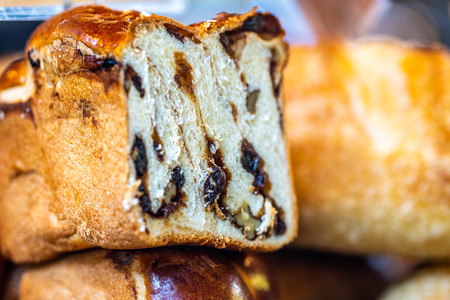 Brioche style sweet loaf with cinnamon, walnuts, raisins. Homemade poppy seed braided bread, close up selective focus. National pastries.