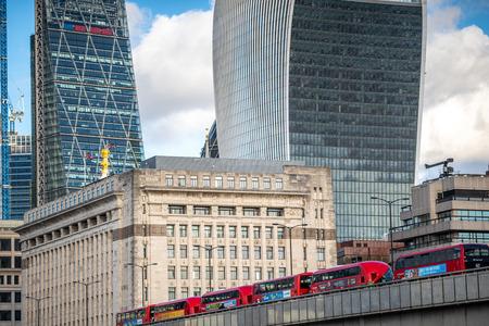 NOVEMBER 13, 2018, London, United Kingdom : Iconic new red London double decker passenger buses on London Bridge feat. Famous Office Buildings