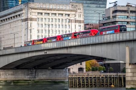 NOVEMBER 13, 2018, London, United Kingdom : Iconic new red London double decker passenger buses over the Thames in London Bridge.