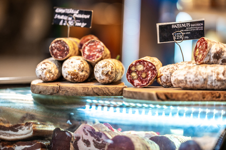 Various types of Dried organic salami sausage and saucisson on wooden cutting board in a store market Banque d'images