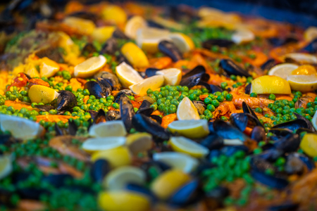 Spanish seafood paella with chicken, mussels, prawns, shrimps and chorizo sausages in traditional pan close up in a food market Banque d'images