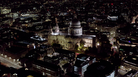 Aerial Night View of St. Pauls Cathedral in London. Birds Eye View Video feat. Religious Iconic Church and Tourism Landmark with traffic on London city streets and orbiting Monument in England, UK