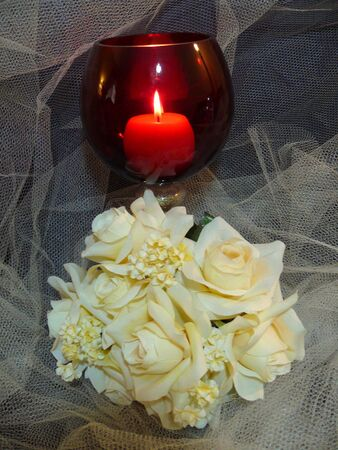 candle holder: a bouquet of cream roses in front of a red candle holder. Stock Photo