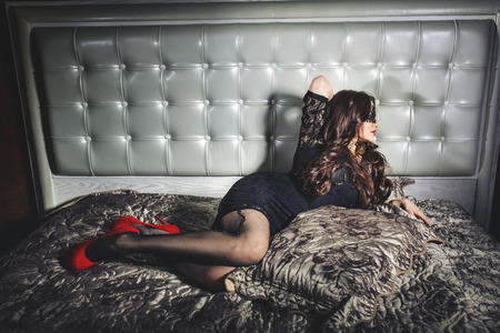 beautiful girl with long hair in blindfold lying on the bed photo