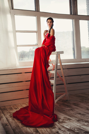 billowing: beautiful girl in a long red dress billowing